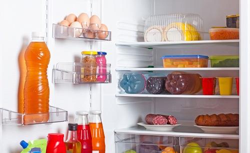 Холодильник с открытой дверцей и продуктами на полках