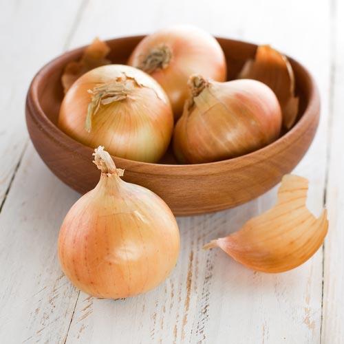 Луковицы и шелуха в деревянной миске