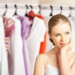 Задумчивая девушка перед шкафом с вещами